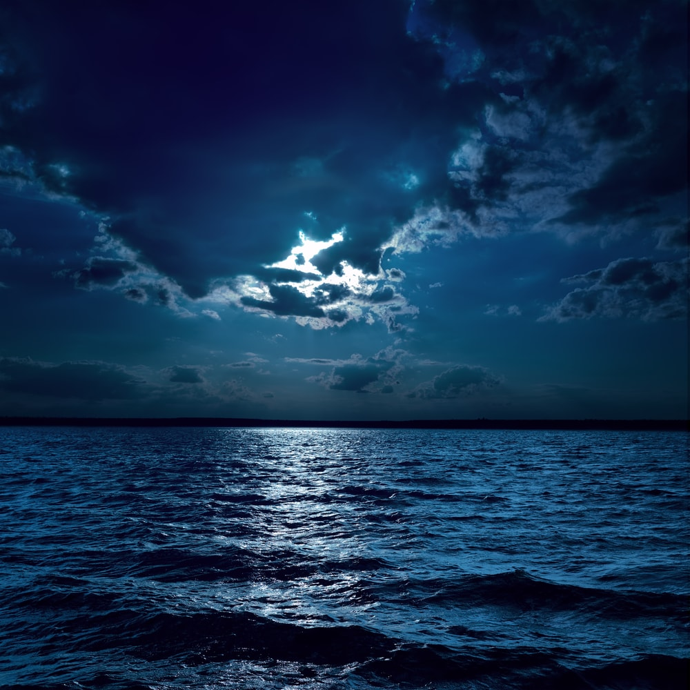 Picture of a calm seas with cloudy skies at night