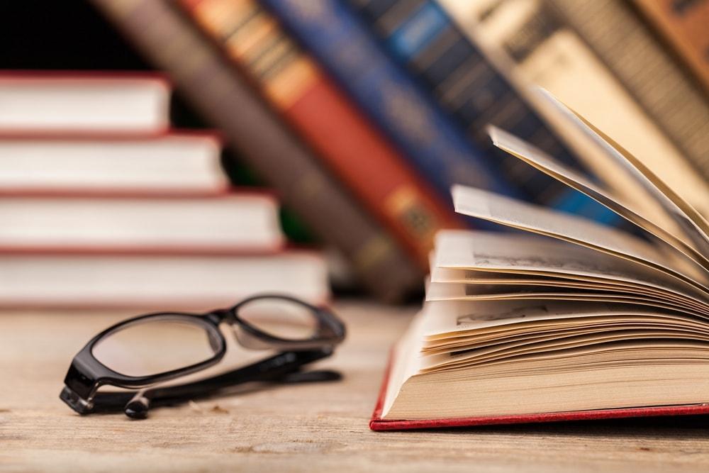 An open book beside an eyeglasses on a wooden table