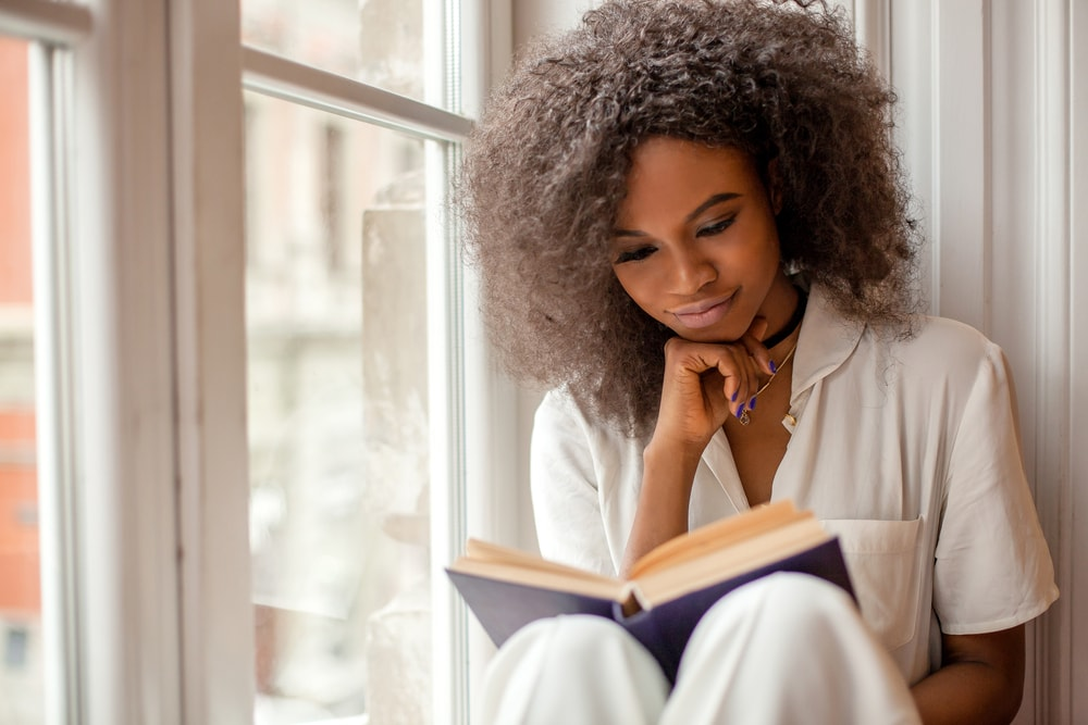 Picture of a woman seated at window sill reading a book
