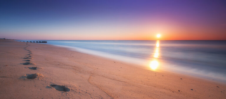 Picture of a sunset from a beach with footprints viewpoint